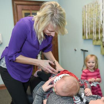 Dr. Amy adjusting infant