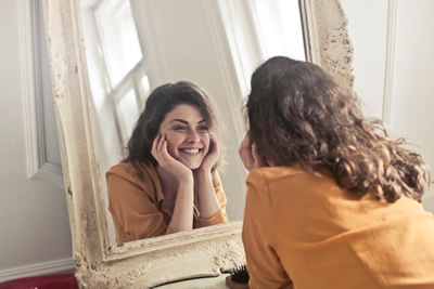 Woman facing mirror smiling with straight teeth