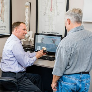 Dr. Brown holding spine model by patient