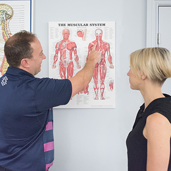 Dr. Brian showing a patient a spinal chart