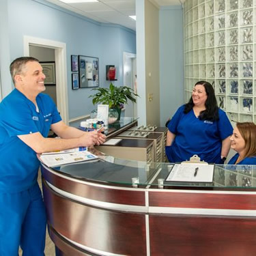 Dr Brian and team smiling at receptionist area
