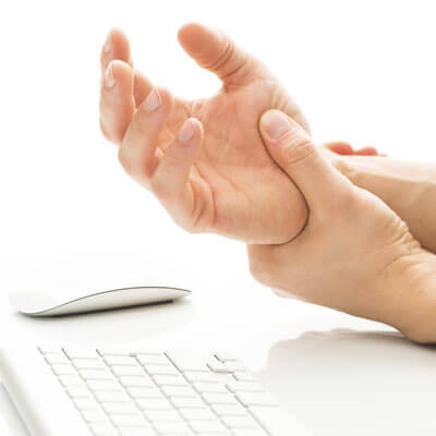 person holding their wrist in pain while using a keyboard and mouse