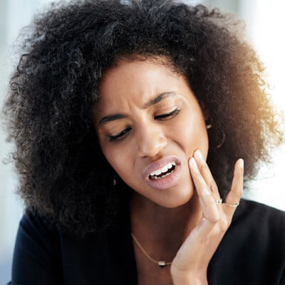 woman with jaw pain touching her jaw