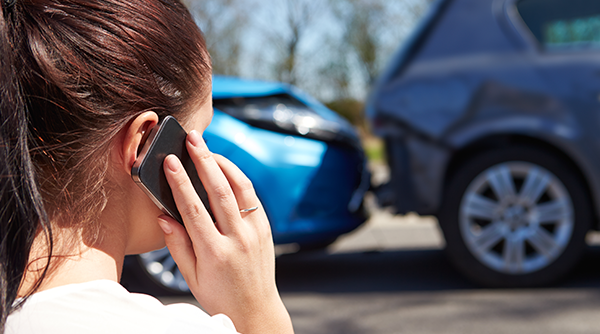 woman on her phone after being in an auto accident