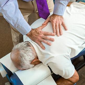 Les mains du Dr Beaudry sur le dos du patient