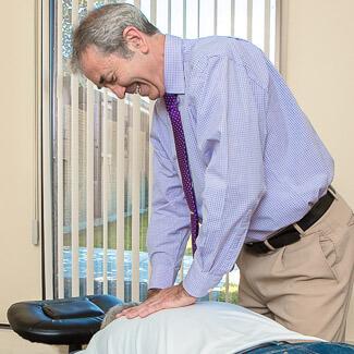 Dr Beaudry posant ses mains sur le dos du patient