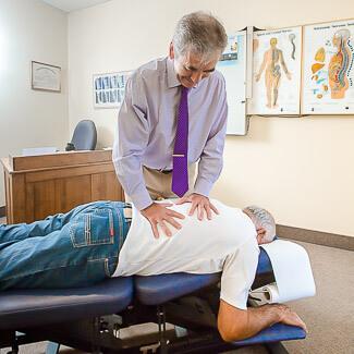 Dr Beaudry ajuste la région du bas du dos du patient