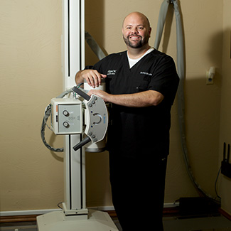 Dr. Kyle standing by xray machine