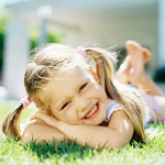 girl-in-piggytails-laying-on-grass-sq-150