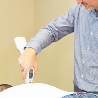 Dr. Mills performing adjustment with activator