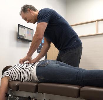 Dr. Gray adjusting woman upperback