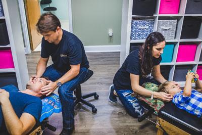 two chiropractors adjusting patients