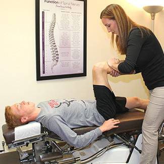 Dr. LaRocque stretching male athlete