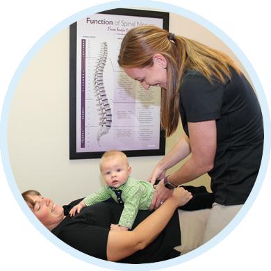 Dr. LaRocque adjusting baby on mom
