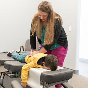 Dr. Alyssa adjusting a little boy