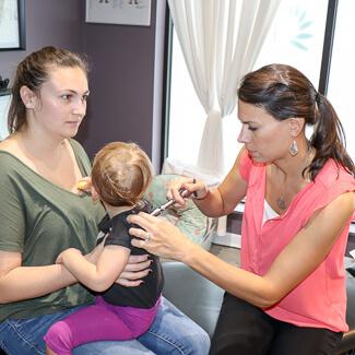 Dr. Andrea activator adjusting toddler