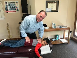 Dr. Maddigan adjusting a boy.