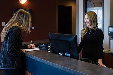 Woman welcoming patient at front desk