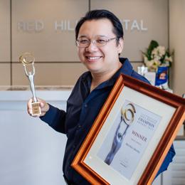 Dr Henry Ho holding awards
