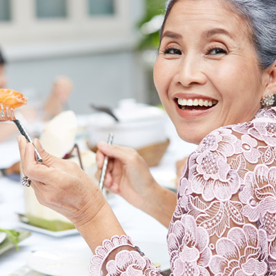 older woman smiling and eating