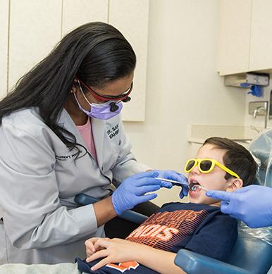 Dr Anu giving dental exam to little boy