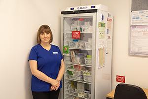Nurse at medicine refrigerator