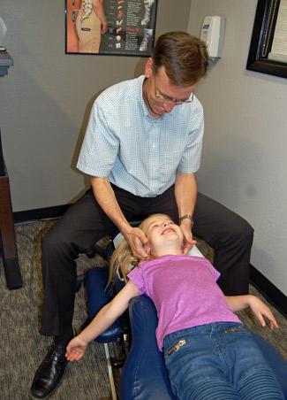 Dr. Bentley adjusting little girl