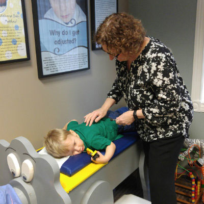Dr. Cathy adjusts young boy