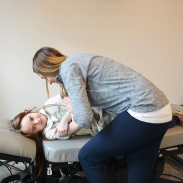 Dr. Amy adjusting a young girl