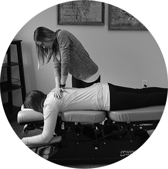 Dr. Amy adjusting a female patient