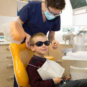Dr Selagea with young boy in dental chair