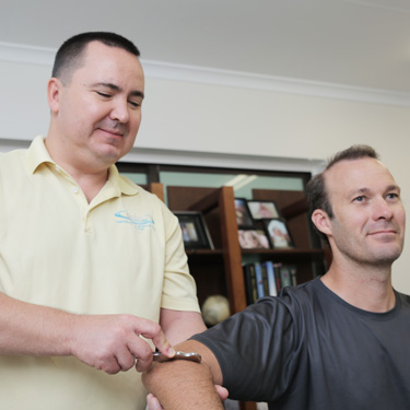 Dr Paul Klich applying myobars technique to a patient's arm
