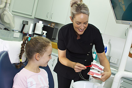 Dental hygienist demonstrating brushing technique to child