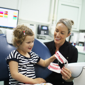 Jackie Edmunds, oral health therapist, instructing child on good brushing technique