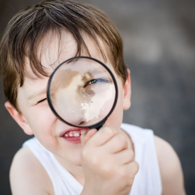 Boy looking at magnifying glass