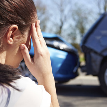 Woman standing outside of car accident