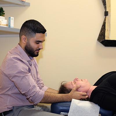 Dr Naweed Miry adjusting patients neck