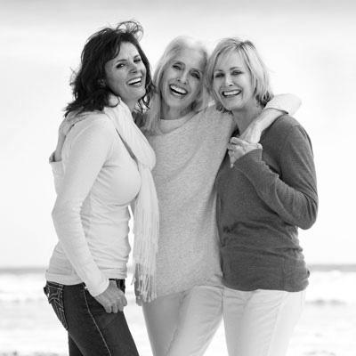 three woman smilling on beach