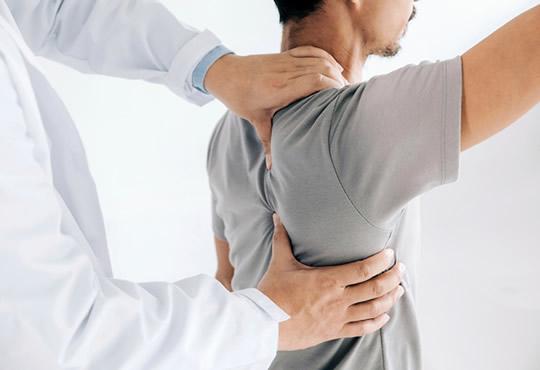 Chiropracor adjusting back shoulder