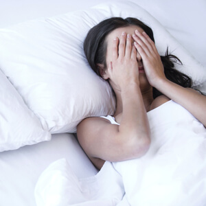 Woman in bed with her hands over her eyes