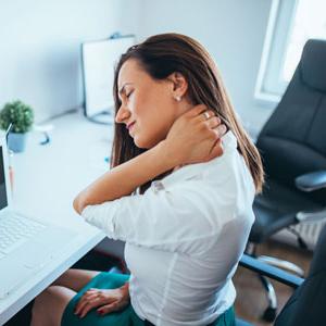 Woman sitting at desk rubbing neck