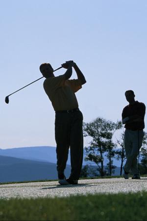 Silhouette of men golfing