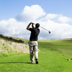 Golfer swinging at ball