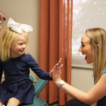 Dr. Kimber high fiving little girl