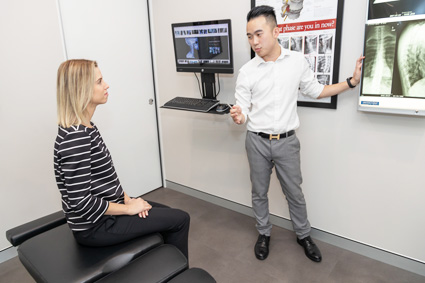 Dr Le looking at xrays with a client