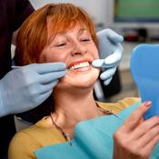 Woman admiring dental work in mirror