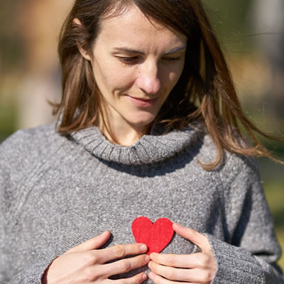 woman-holding paper heart on chest