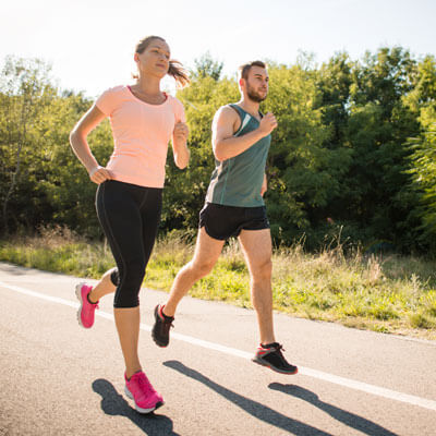 man and woman running on a road