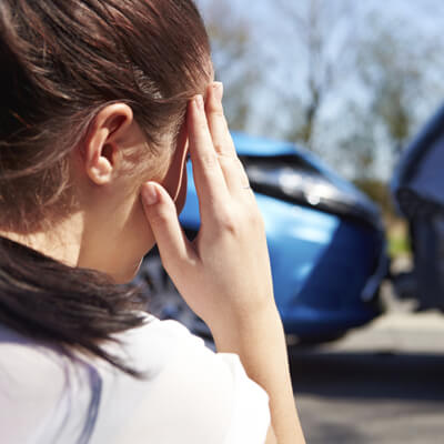 Woman holding forehead after car accident