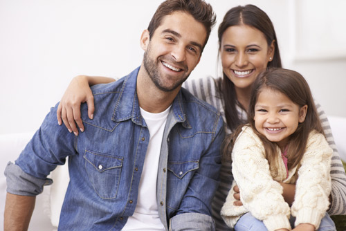 man with wife and young daughter smiling